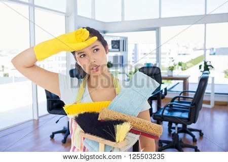 Weary woman holding cleaning tools against board room