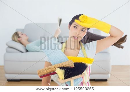 Weary woman holding cleaning tools against attractive blonde woman reading newspaper lying on couch