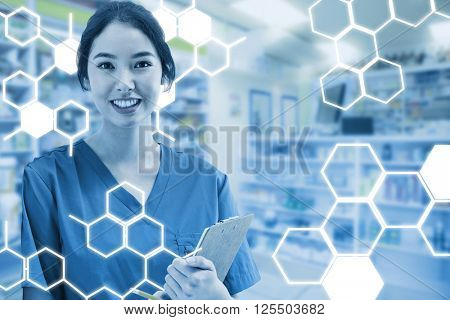 Asian nurse with stethoscope looking at the camera against a white screen against close up of shelves of drugs