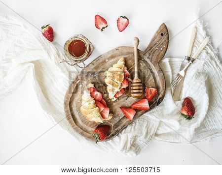 Freshly baked croissants with strawberries, mascarpone and honey on rustic wooden board over white backdrop, top view, horizontal