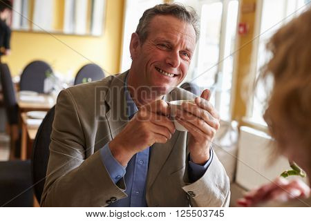 Senior couple drink coffee at restaurant, over shoulder view