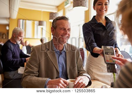 Senior couple making card payment to waitress in restaurant