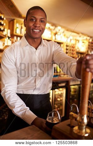 A young black man working behind a bar looks to camera