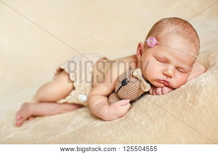 Carefree little boy with a pink flower on his head wearing a knitted beige panties, with their legs at the knees and putting the handle under his cheek,sleeping sweetly on a soft beige blanket hugging bear toy beige