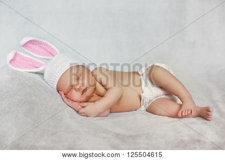 Beautiful baby in a white knitted hat with pink Bunny ears, white knit panties with a round rabbit tail between his legs little feet, sleeping on a soft gray blanket,his hands under his cheek