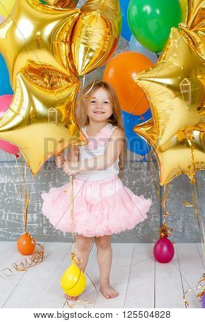 Beautiful child,redhead girl with long straight hair and grey eyes, with a pink bow on her head, dressed in pink and white dress on a white background with multi-colored balloons and gold stars to your fourth birthday