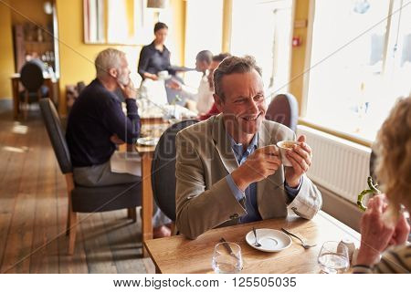 Senior couple have coffee at restaurant, elevated view