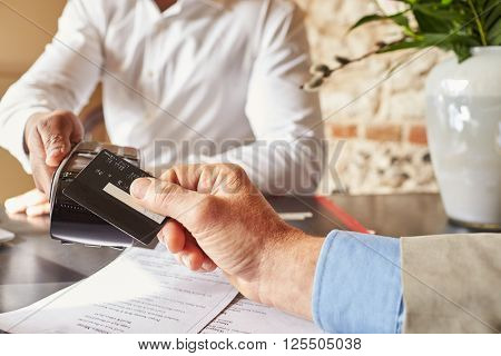 Guest making contactless card payment at hotel, hands detail