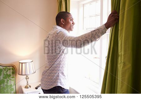 Man opens curtains to look at the view from a hotel window