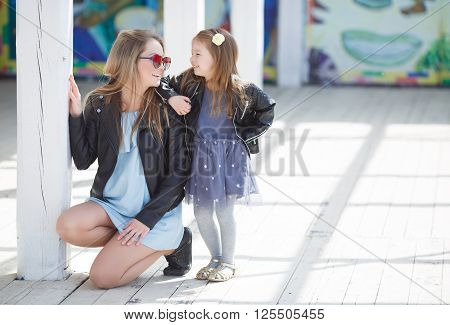 Happy mother and her little daughter four years of age, both blonde with straight long hair,both dressed in fashionable leather jackets in black and a light summer dress, mom's got dark sun glasses,spend time together outside in the spring