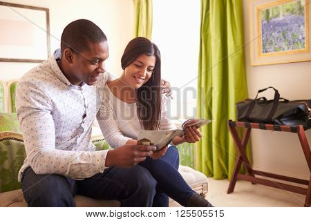 Young couple read a guide brochure together in a hotel room
