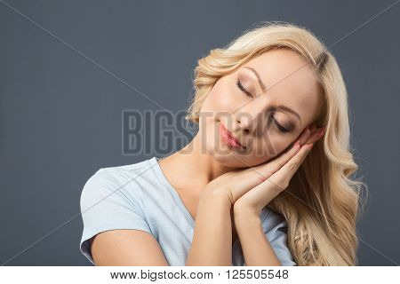 Time to sleep. Pleasant content young girl holding her palms together and closing her eyes while having wish to sleep