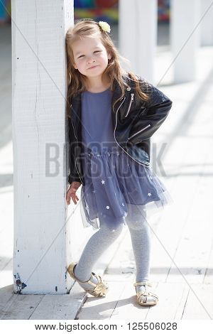 Portrait of a little girl with pale straight hair,wearing a leather jacket of black color and gray-blue gown,in her hair wears a white flower, posing to photographer on a Sunny day in the city outdoors in the spring