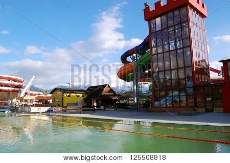 LIPTOVSKY MIKULAS SLOVAKIA - JANUARY 17 2015: Red tower and big swimming-pool with green thermal water in new aquapark in Liptovsky Mikulas Slovakia.