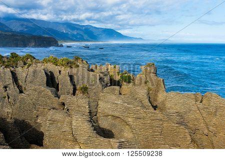 Pancake Rocks in Paparoa National Park New Zealand. Seascape with layered rock formation. Punakaki rocks are nature wonder and famous tourist destination of South Island New Zealand