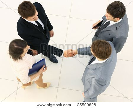 Business meeting. Top view of four people in formalwear standing close to each other while two of them handshaking