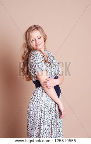 Smiling girl 22-24 year old posing in room over beige. Wearing trendy dress with floral pattern. Young adults.