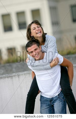 Portrait of a smiling young man carrying a young woman