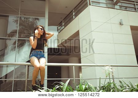 Cheerful young woman sitting on railing and talking on phone with friend