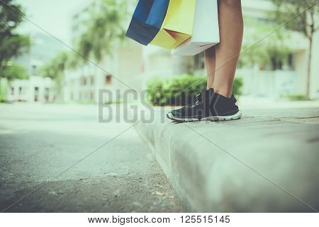 Feet of female shopaholic carrying her purchases