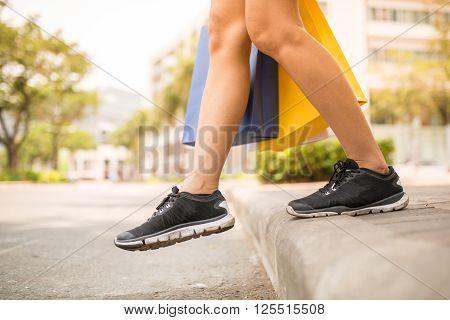Female shopaholic in sport shoes crossing road