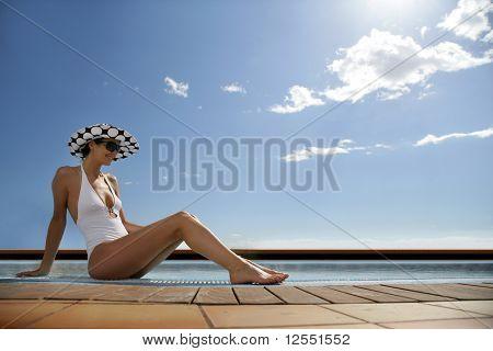 Portrait einer jungen Frau im Badeanzug sitzen an einem Pool