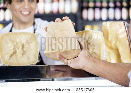Salesman's Hand Passing Cheese To Colleague In Shop
