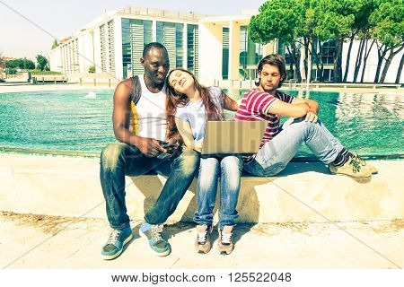 Multiracial friends with pc laptop outdoors in funny jealousy scene - Afro american man and white teenagers friends sitting with computer near fountain - Vintage filter look with pastel tones