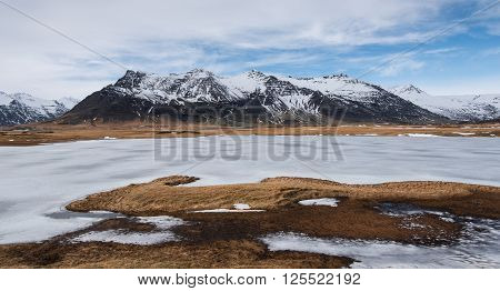 Typical Icelandic mountain landscape in Southeast Iceland with frozen lake