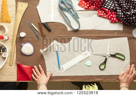 Desk designer fashion. Fashion designer starts cutting fabric to create fashionable clothes.