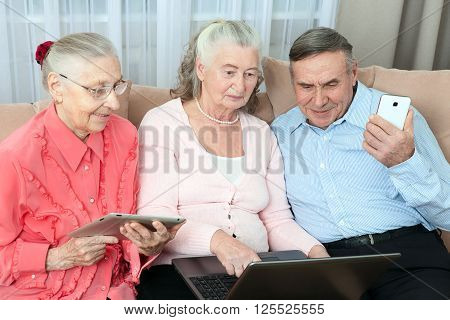 Group of elderly people. Group of older people having fun in communicating with the family on the internet in the comfortable living room. Concept an active life in retirement