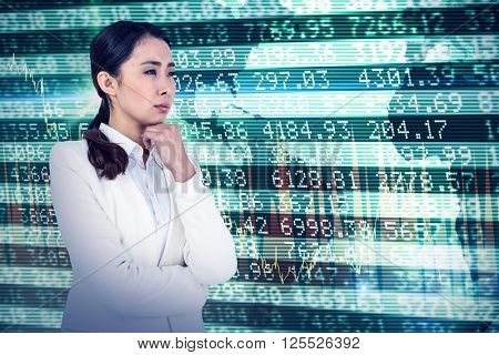 Asian businesswoman touching her chin against stocks and shares