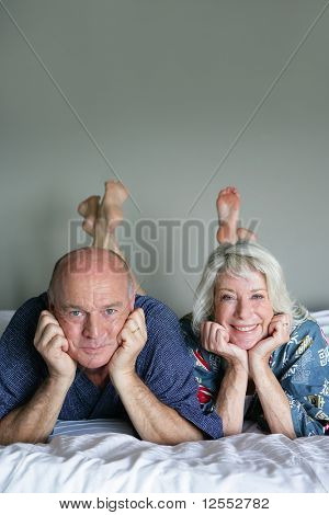 Portrait of a senior couple lying on a bed