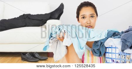 Frowning woman taking out dirty laundry against low section of businessman resting on sofa in living room