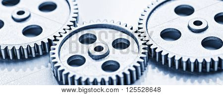 Two large and a small gear wheel which overlap.