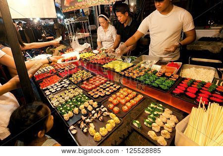 CHIANG MAI, THAILAND - FEBRUARY 20, 2016: People making choice at Sushi stall with seafood delicacies on the city night market on February 20, 2016. Population of Lampang is near 59000 people