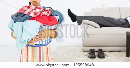 Tired woman holding full laundry basket against low section of a businessman resting on sofa in living room