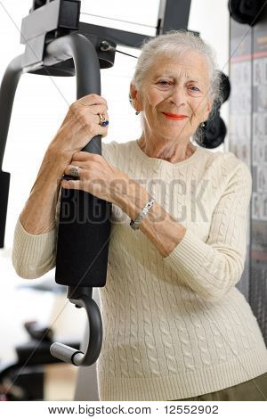 Senior Woman With Fitness Machine Over White Background