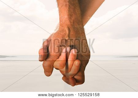 Happy senior couple holding hands against cross religion symbol shape over sunset sky at the beach