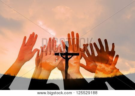 People raising hands in the air against cross religion symbol shape over sunset sky