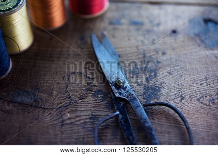 Old scissors and sewing thread reels or bobbins on a old rustic work bench. Intentionally shot in low key tone and shallow depth of field. (soft focus). Focus on scissors pivot.