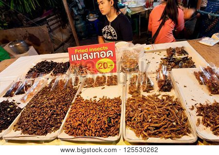 CHIANG MAI, THAILAND - FEBRUARY 20, 2016: Woman selling fried grasshoppers and edible insect larvae at traditional thai night market on February 20, 2016. King Mengrai founded the city of Chiang Mai in 1296