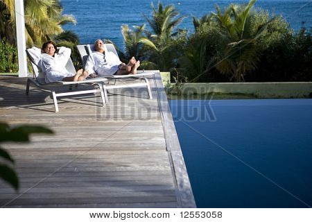 Senior couple in bathrobe lying on deck chairs next to a swimming pool