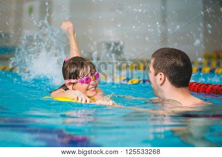 instructor teaches the girl swimming in a pool.