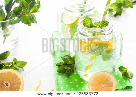 Lemonade with mint in a mason jar on a white background. Summer drink.