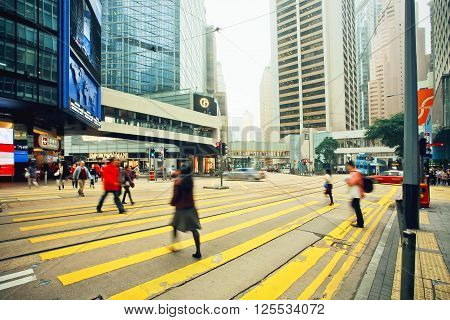 HONG KONG, CHINA - FEBRUARY 12, 2016: People walking on streets with tall glass and concrete buildings in busy district of asian city on February 12, 2016. There are 1223 skyscrapers in Hong Kong.