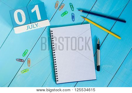 July 1st. Image of july 1 wooden color calendar on blue background. Summer day. Empty space for text.