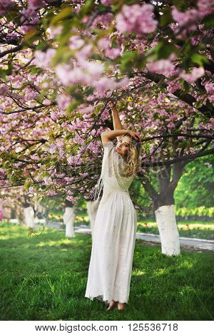 Spring Beauty Girl With Long Red Blowing Hair Outdoors. Blooming Sakura Tree. Romantic Young Woman P
