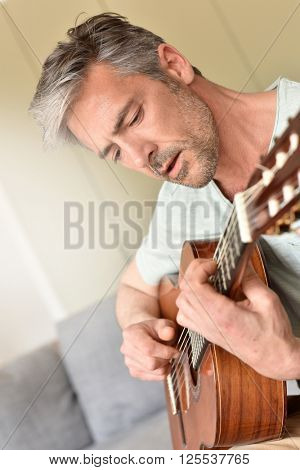 Man playing acoustic guitar at home