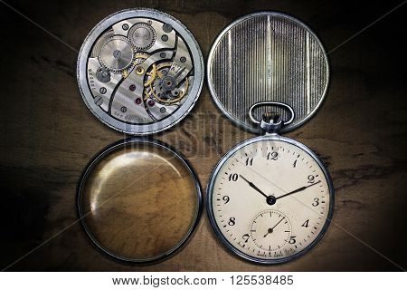 Old russian pocket watch inside and covers on wooden table